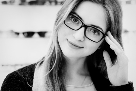 closeup of a face of young woman with glasses looking to the camera, black and white image