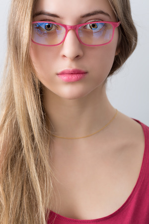 portrait of young wooman with pink glasses, lips and shirt - matching color palette