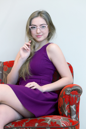 young woman with pink glasses sitting on a sofa Stock Photo