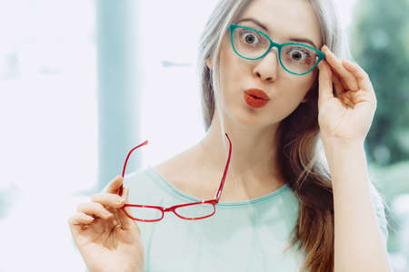 young woman with funny face trying on different pairs of eyeglasses - red and aquamarine Stock Photo