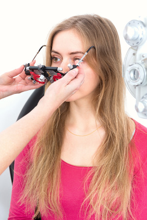 young woman during eyes examination with diagnostic frame in a optometric clinic