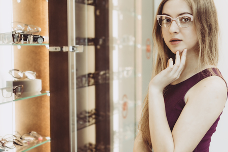 woman with glasses in the optical salon standing next to showcase full of frames