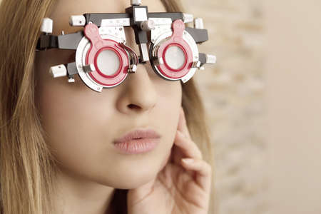 face of a young woman during eyes examination with diagnostic frame in a optometric clinic
