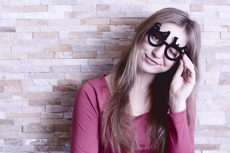 smiling woman with glasses shaped into SALE text looking straight to the camera and blinking an eye
