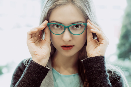 opthalmology: portrait of young woman trying the glasses on - aquamarine color style, high-key