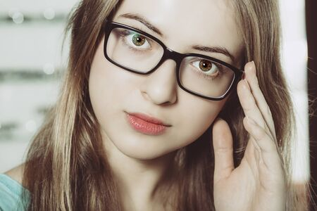 closeup of a face of young woman with black glasses looking to the camera