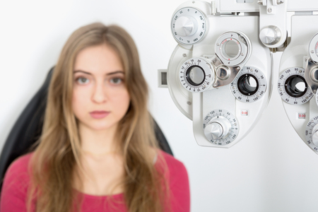 woman patient waiting for eye examination with phoropter at optometrist clinic - sharpness on phoropter