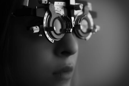 face of a young woman during eyes examination with diagnostic frame in a optometric clinic - black and white low key