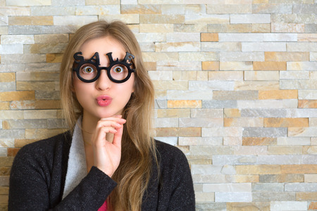 surprised blonde woman with big open eyes and funny face with glasses shaped into SALE text Stock Photo