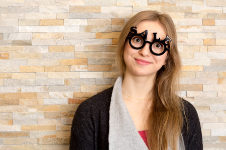 opthalmology: smiling woman with glasses shaped into SALE text looking straight to the camera with big open eyes