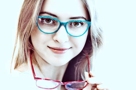 young woman trying on different pairs of eyeglasses - blue and red