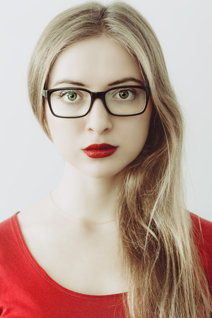portrait of young wooman with black glasses and red lips and shirt