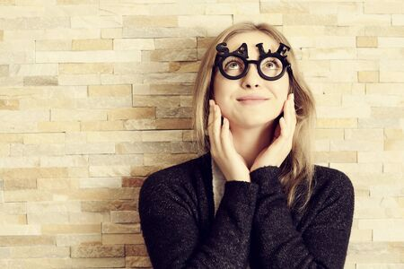 opthalmology: amazed woman with glasses shaped into SALE text looking up with emotions