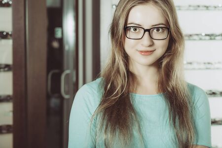 woman with glasses in the optical salon standing and smiling to the camera