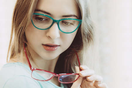 young woman trying on different pairs of eyeglasses - aquamarine and red