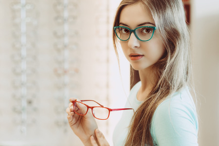 opthalmology: young woman trying on different pairs of eyeglasses - aquamarine and red