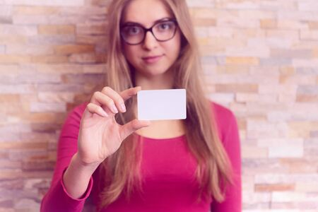 opthalmology: young blonde girl with glasses showing blank business card - pink tones