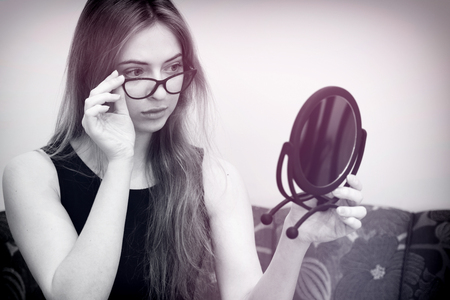 woman with glasses looking in the mirror, black and white with delicate pink colour