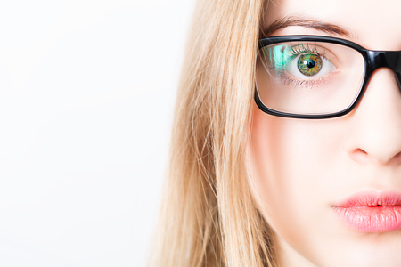 closeup of and eye and brown iris of blonde woman with black glasses Stock Photo