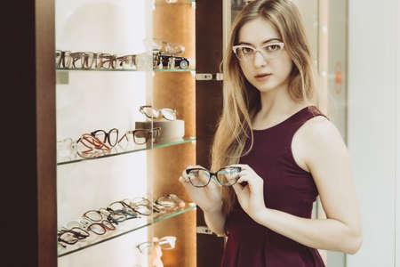opthalmology: woman with glasses in the optical salon standing next to showcase full of frames and testing second pair of frames