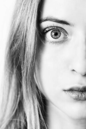 closeup of a womans eye - vertical half of a face, black and white Stock Photo