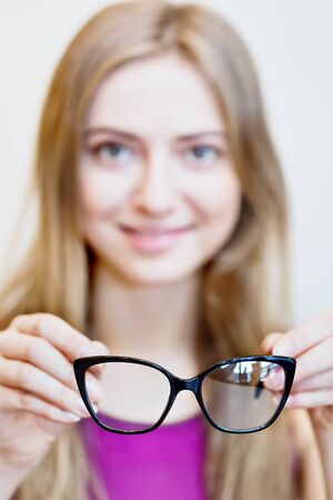 black eyeglasses in hands of a blonde smiling woman - sharpness on glasses