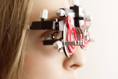 young woman during eyes examination with diagnostic frame in a optometric clinic, closeup