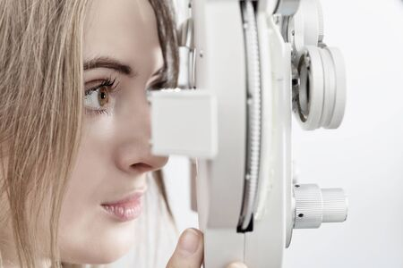 woman patient waiting for eye examination with phoropter at optometric clinic Stock Photo