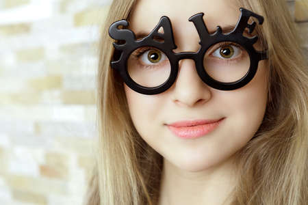 smiling woman with glasses shaped into SALE text looking straight to the camera