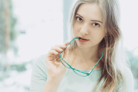 portrait of young woman with glasses in hand - aquamarine color style, high-key