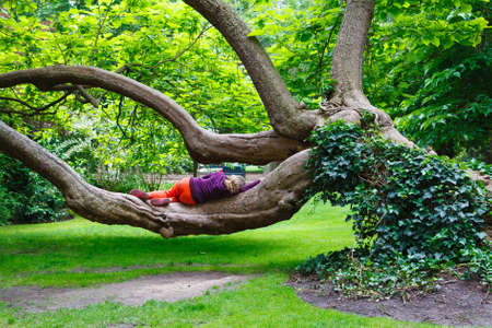 Paris, France, Luxembourg Gardens: woman laying and resting on a big tree in the Luxembourg Gardens