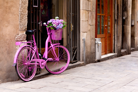 pink bicycle standing on the street - some flowers in the basket Stock Photo