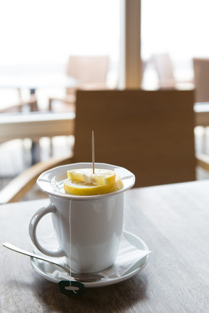 in the caffee - mug of tea with lemon, free empty chairs Stock Photo