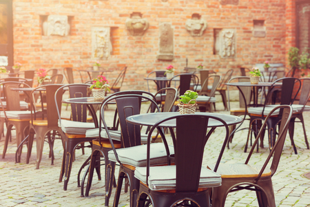 Outside Patio Of An European Restaurant   Tables And Chairs On The Street  In Bright Sunlight