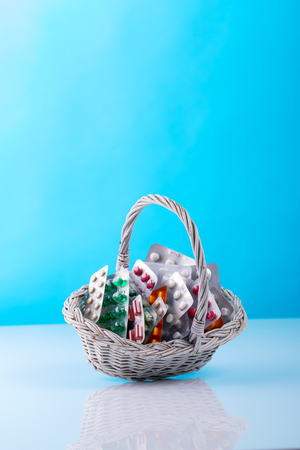 old basket full of blisters with pills on blue background