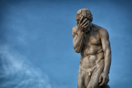 Henri Vidals Statue of Cain - gardens Tuileries, Paris, France- sadness (or facepalm) on blue sky background