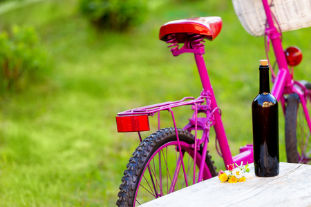 bottle of red wine and pink bike with white basket - picnic scene on green grass