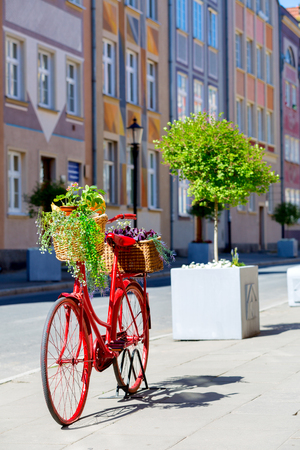 an old stylized red bike with baskets full of flowers standing on the street Stock Photo