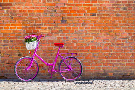 pink bike with white basket full of flowers standing by the brick wall