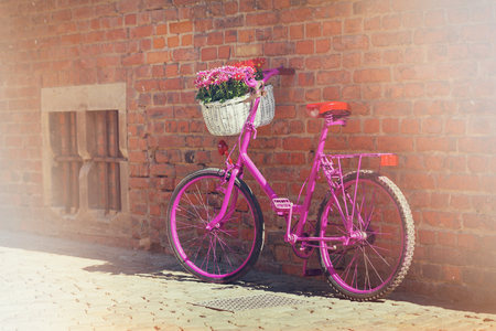 pink bike with white basket full of flowers standing in bright light by the brick wall Stock Photo
