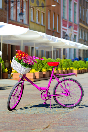pink bike standing on an old street of an old town in Gdansk, Poland Stock Photo