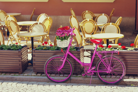 pink bike standing on an old street next to restaurants tables on an old town in Gdansk, Poland Stock Photo