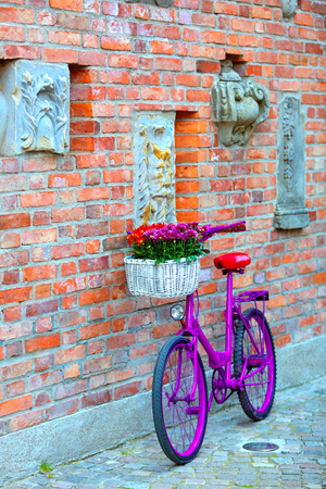 pink bike with white basket full of flowers standing by the brick wall Stock Photo