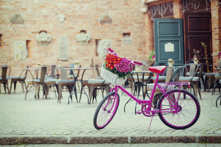 pink bike standing on a place next to the restaurant on an old town in Gdansk, Poland Stock Photo