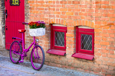 pink bike with white basket full of flowers standing by the brick wall next to red door and windows