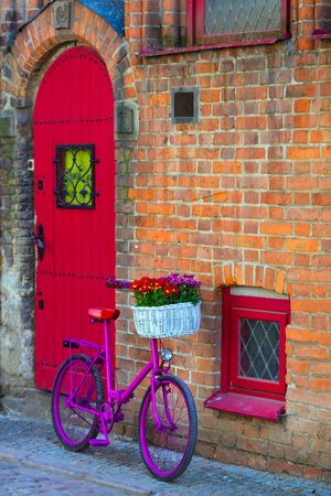 pink bike with white basket full of flowers standing by the brick wall next to red door and window