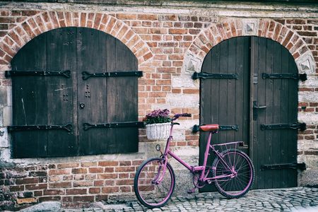 pink bike with white basket full of flowers standing by the brick wall next to old wooden door and window Stock Photo
