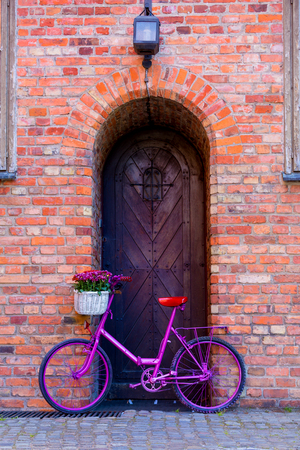 pink bike with white basket full of flowers standing by the brick wall next to old wooden door  Stock Photo