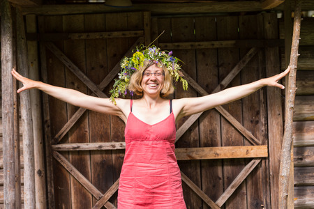 young adult woman with wreath standing with open arms in front of the wooden shed