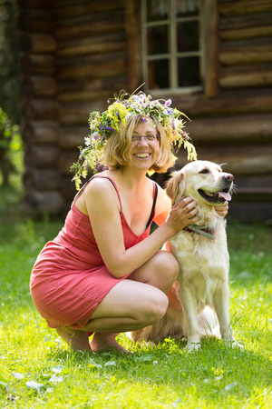 young woman with wreath on her head and a dog, golden retriver Stock Photo